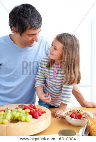 Padre afectuoso y su hija desayunando