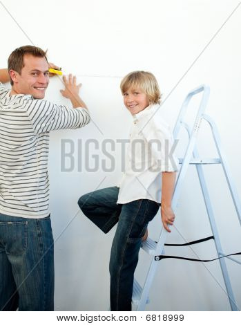 Smiling Father And His Son Decorating A Room