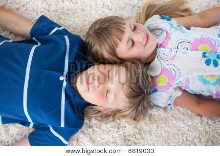 Cute Siblings Lying On The Floor