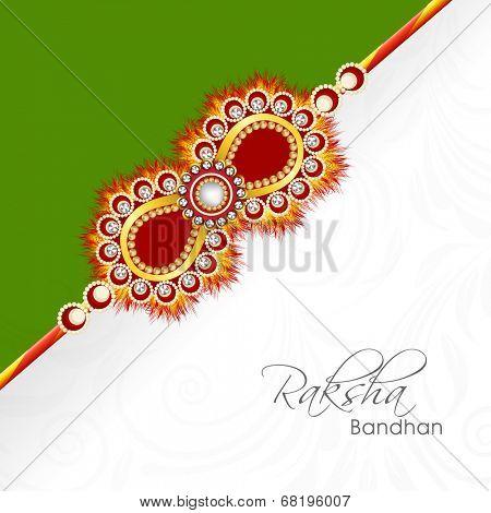 Beautiful golden rakhi on green and floral decorated grey background for Raksha Bandhan celebrations.