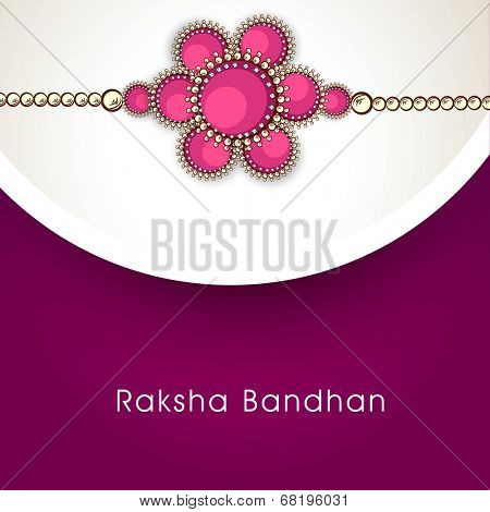 Beautiful rakhi on grey and purple background for Happy Raksha Bandhan celebrations.
