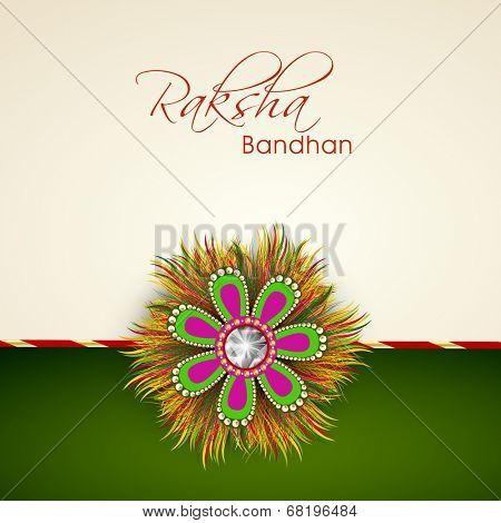 Beautiful rakhi on beige and green background for Happy Rakhsha Bandhan celebrations.