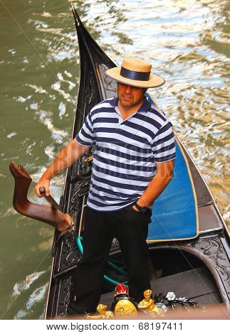 Gondolier In A Gondola Sailing On Canal In Venice, Italy