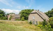 stock photo of neglect  - Abandoned and neglected historic farmhouse down a Dutch embankment - JPG