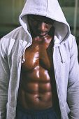 foto of pectorals  - Muscular young man in hood jacket at the gym - JPG
