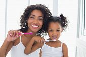 picture of pajamas  - Pretty mother with her daughter brushing their teeth at home in the bathroom - JPG