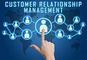 stock photo of customer relationship management  - Customer Relationship Management concept with hand pressing social icons on blue world map background - JPG