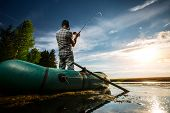 pic of jerks  - Mature man fishing from the boat at sunset - JPG