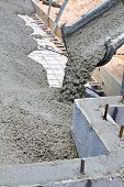 stock photo of chute  - Wet cement pours down a concrete truck chute to fill a slab at a home building construction site - JPG