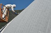 pic of cherry-picker  - Tradesman spray painting the roof of an industrial building - JPG