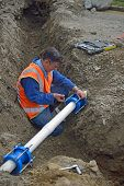 foto of plumber  - Plumber tightens the joiners on pipes for a broken stormwater drainage system - JPG
