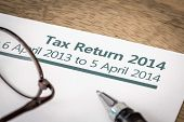pic of self assessment  - UK Income tax return form for 2014 on a desk with pen and glasses - JPG