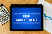 stock photo of dangerous situation  - risk assessment word on digital tablet with calculator and financial graph - JPG