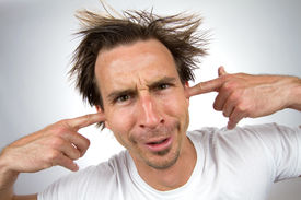 picture of noise pollution  - Scruffy unpleasant looking man with a silly facial expression and unruly hair puts his fingers in his ears so that he can not hear - JPG