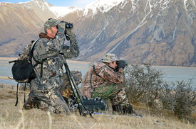 stock photo of hunter  - Hunters scoping for Himalayan tahr in the Southern Alps of New Zealand