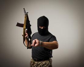 picture of terrorist  - Terrorist with gun looking at his wristwatch - JPG