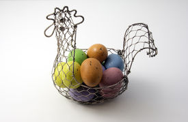 stock photo of chicken-wire  - wire basket shaped like a chicken full of colored Easter eggs - JPG