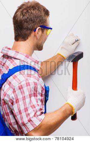Back shot of repairman nailing