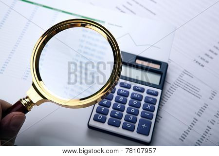 Man Considers The Budget Through A Magnifying Glass