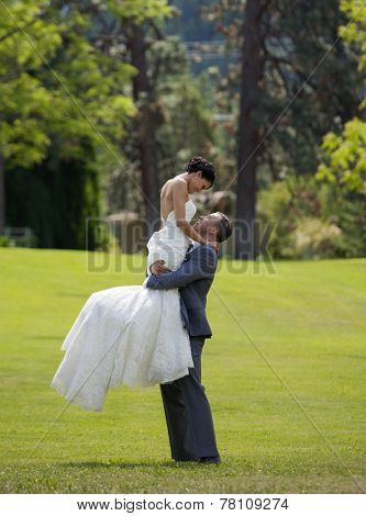 Groom lifting bride in outdoor garden setting