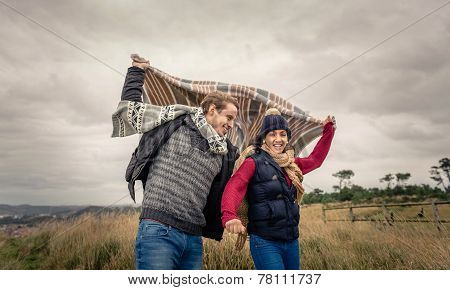Young couple playing outdoors with blanket in a windy day