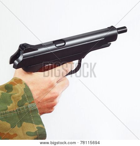 Hand in camouflage uniform with discharged handgun on white background