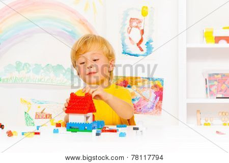 Handsome blond boy playing with plastic blocks