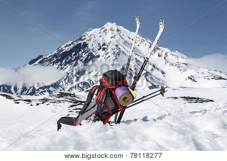 Backpack, Skis And Poles Lie On The Snow On Background Volcano