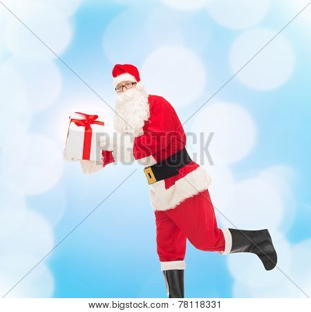 christmas, holidays and people concept - man in costume of santa claus running with gift box over blue lights background