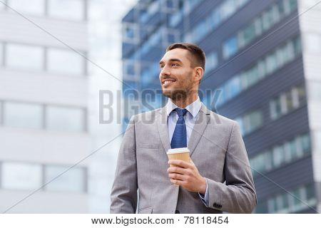 business, hot drinks and people and concept - young smiling businessman with paper coffee cup over office building