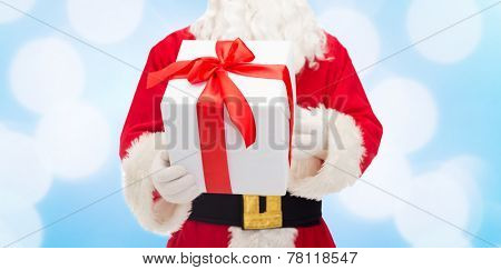 christmas, holidays and people concept - close up of santa claus with gift box over blue lights background