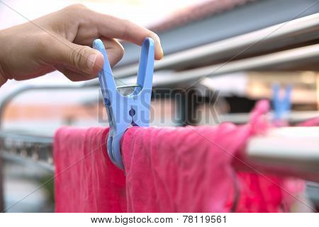 Hand using cloth peg to hang a washed red polyester rag