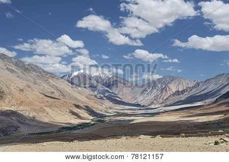 Small Green Village And River Among Majestic Desert Mountains
