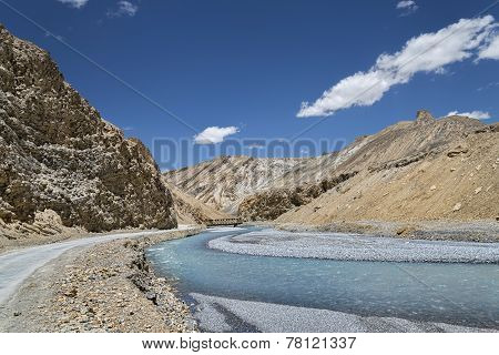 Curved River In Mountains And Winding Road Nearby