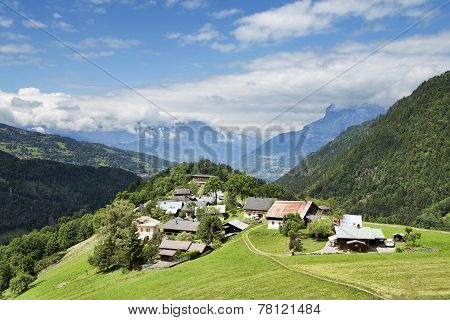 Scenic Landscape With Little Alpine Village On Green Hill