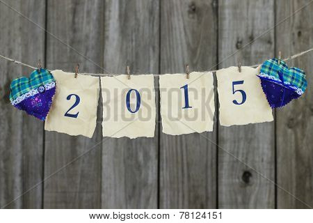 Year 2015 in blue on antique parchment paper hanging on clothesline with fabric hearts by wood fence