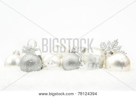 Silver Christmas Decoration On Snow In Line