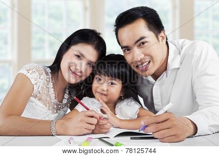 Girl Doing Homework With Her Parents