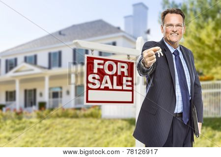 Real Estate Agent with House Keys in Front of For Sale Sign and Home.