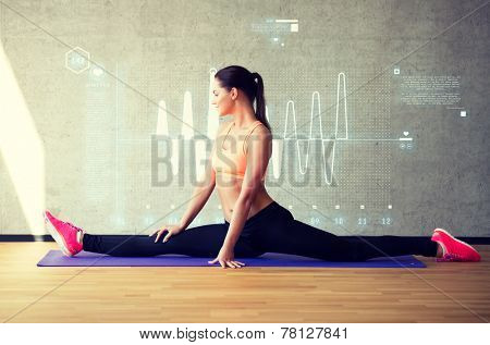 fitness, sport, training, future technology and lifestyle concept - smiling woman stretching leg on mat in gym over cardiogram projection