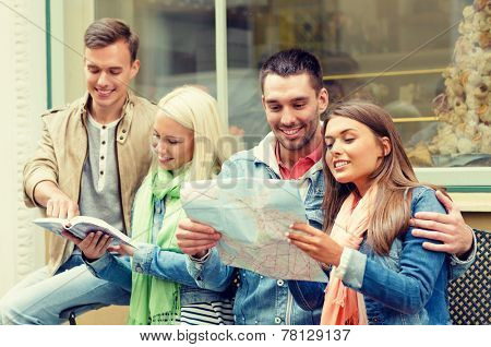 travel, vacation and friendship concept - group of smiling friends with city guide and map exploring town
