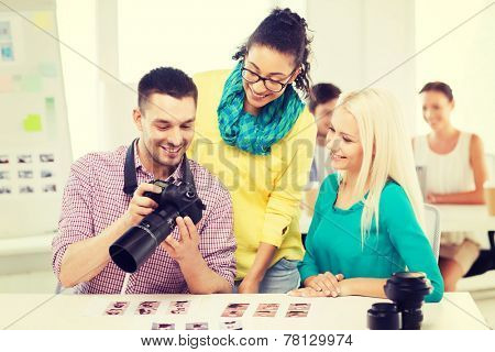 business, education, photography, office and startup concept - smiling creative team with photocamera working in office