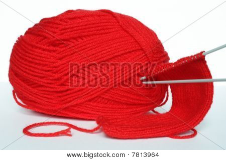 Red clew of sewing and knitting needles