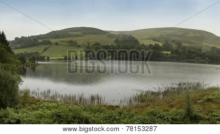 Landscape Panorama Of Lake With Rolling Hills In Background