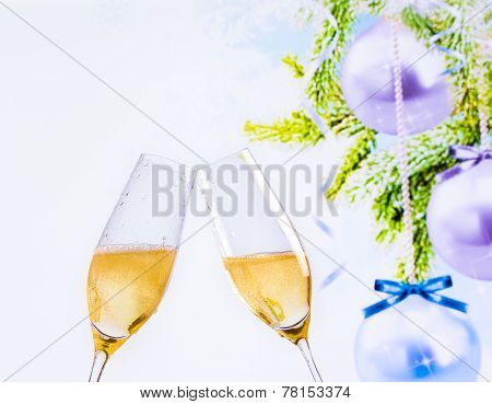Champagne Flutes With Golden Bubbles On Christmas Tree Decoration Background