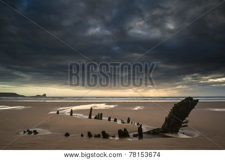 Landscape Image Of Old Shipwreck On Beach At Sunset In Summer
