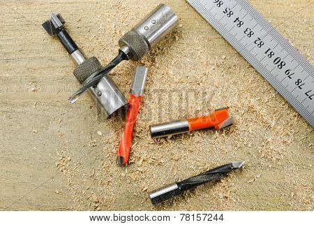 Drill Bits And The Scale On A Wooden Background