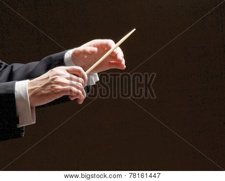 Concert conductor hands with a baton isolated on a black background