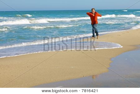 Man runs in red t-shirt on sand on seashore
