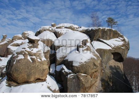 Rocks in snow under clouds